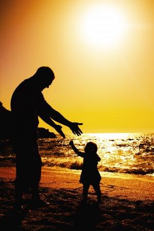 day of father: padre e figlia che giocano sulla spiaggia al tramonto Archivio Fotografico