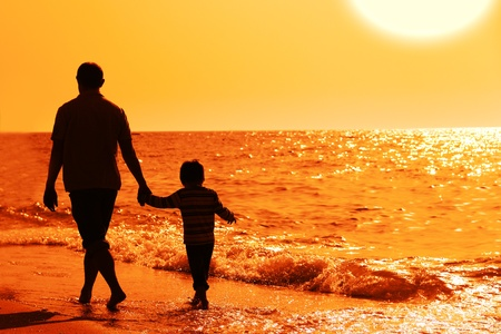 father and son on sunset at the beach Stock Photo