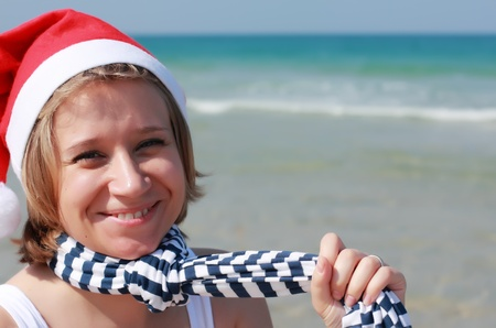 Christmas at sea. Girl in Santa hat on the beach photo