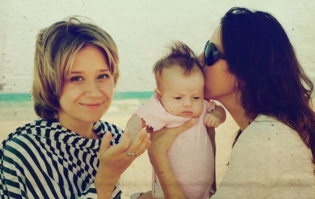 three months old: two beautiful girls with a baby on the beach