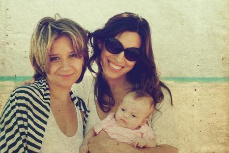 lesbianas: dos hermosas chicas con un bebé en la playa de estilo antiguo color de la imagen.