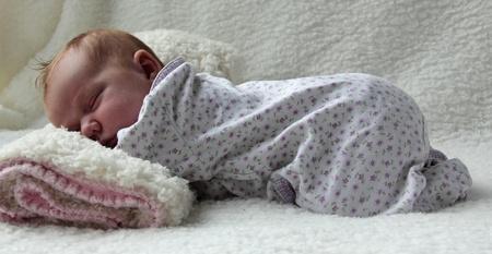 Monatlich Redhead Mädchen schläft auf einer weißen Decke Lizenzfreie Bilder