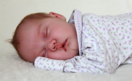 0 6 months: Monthly Redhead baby sleeping on a white blanket Stock Photo