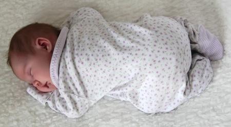 black newborn: monthly child lies on a white blanket