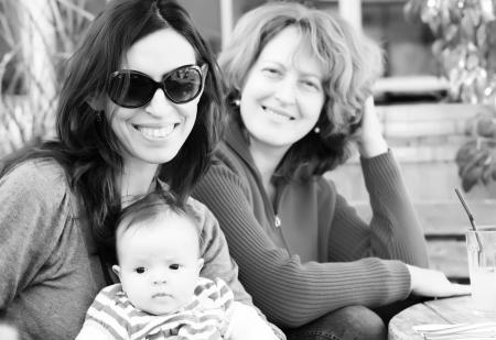lesbianas: dos hermosas chicas con un beb� al aire libre