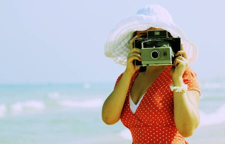 young girl in red dress with old camera photo
