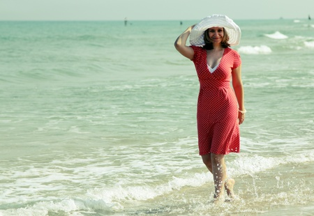 young girl in white hat and red dress on the beach photo
