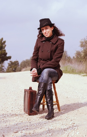 Girl with a suitcase sitting on a stool photo