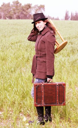 Girl holding suitcase and stool photo