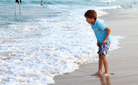 7 Jahre altes Kind kommt auf den Rand des Wassers, Sonnenuntergang Farben