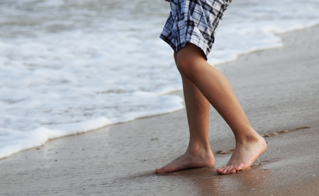boy feet: 7 years old kid coming to the waters edge, sunset  colors Stock Photo