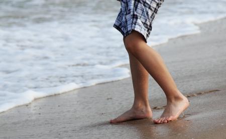 descalza: Ni�o de 7 a�os de llegar a la orilla del agua, los colores de la puesta del sol