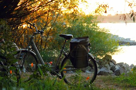 old bicycle: Old and vintage bicycle near the river in sunset colors  Stock Photo