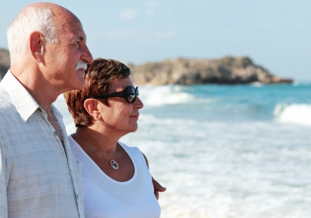 Happy senior couple walking together on a beach photo