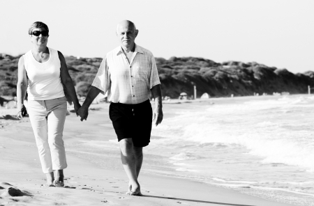 human kind: Happy senior couple walking together on a beach