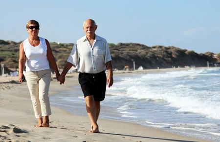 Happy senior Paar zusammen spazieren am Strand Lizenzfreie Bilder