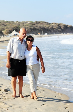 Happy senior couple walking together on a beach Stock Photo - 15299644