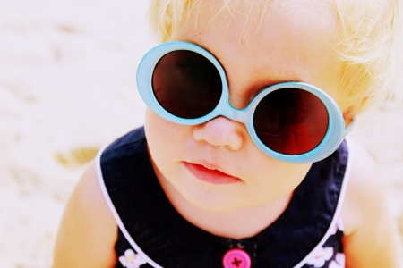 glasses in the sand: Portrait of cute baby with fashin vintage sunglasses  sunglasses worn on the contrary