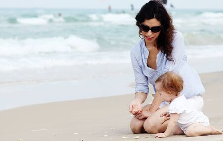 Mother and little baby having fun on the beach photo