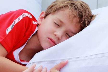 cute 7 years old boy sleeping on white pillow in summer cafe