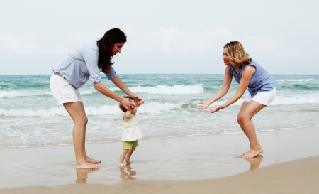 lesbians: two beautiful girls with a baby on the beach