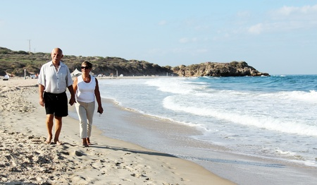 senior couple walking together on a beach photo