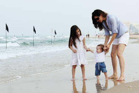 Mother with two daughters on the beach photo