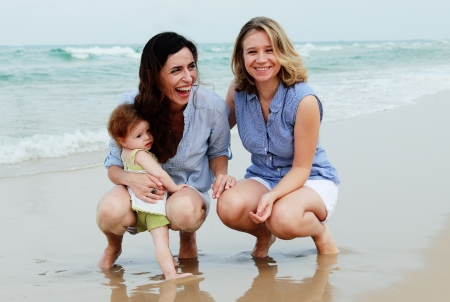 two beautiful women with a baby on the beach Stock Photo