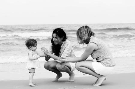 homosexual couple: two beautiful girls with a baby on the beach