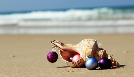 Weihnachtskugeln und Muschel am Strand Standard-Bild
