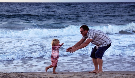 father and daughter playing together on the beach at sunset photo
