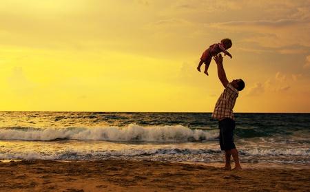 Vater und Tochter spielen zusammen am Strand bei Sonnenuntergang Standard-Bild