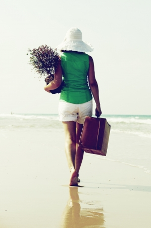 young woman with a tree and a vintage suitcase walking on the edge of the sea photo
