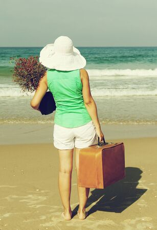 young woman with a tree and a vintage suitcase walking on the edge of the sea in the direction of the big city photo