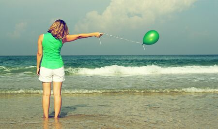 Beautiful girl with green balloon on the beach  Old style colours  photo