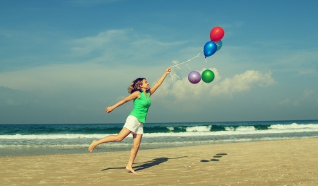 Beautiful girl with a balloons on the beach  Old style colours   photo