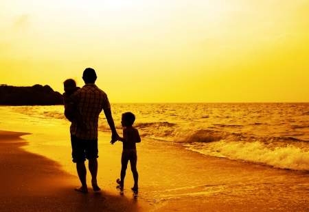 Father and two kids silhouettes on the beach at sunset