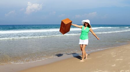Beautiful girl with vintage suitcase on the beach photo