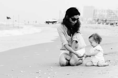 kids feet: Mother and little daughter on the beach Stock Photo
