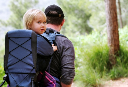 Father hiking with kid on backpack