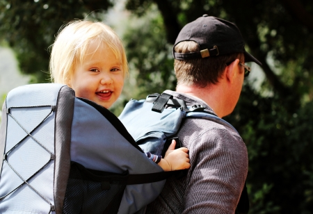 Father hiking with kid on backpack photo