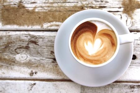Tasse Kaffee auf alten Holztisch am Strand