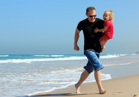 father and daughter on the beach photo