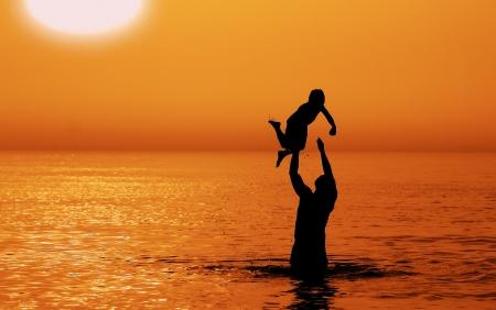 父と息子夕焼けの海に 写真素材