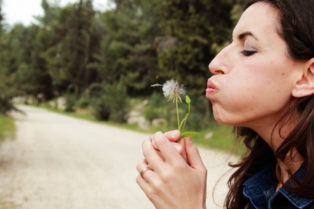 portrait young woman blowing dandelion photo