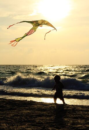 Kid playing with kite on the sea photo