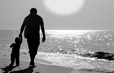 Papa und Kind am Strand bei Sonnenuntergang