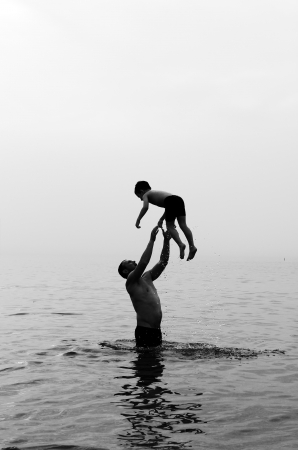 父と息子の夕暮れ時、海で泳ぐ 写真素材