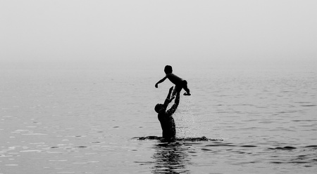father and son swimming in the sea at sunset photo
