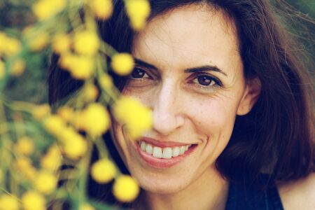 Portrait of smiling woman outdoors with yellow flowers photo